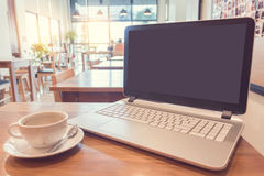 White cup of hot coffee with laptop on wooden table in cafe. Royalty Free Stock Photography