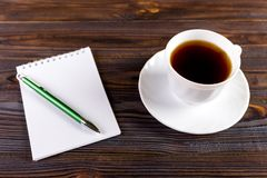 White cup of hot coffee and white sketch book on wood table.  Royalty Free Stock Photos