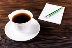White cup of hot coffee and white sketch book on wood table.  Royalty Free Stock Photography