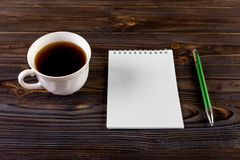 White cup of hot coffee and white sketch book on wood table.  Stock Images