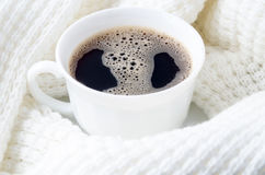 White cup of hot coffee surrounded by a white woolen scarf Stock Images
