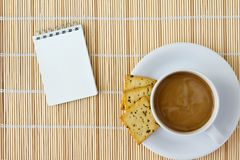 White cup of hot coffee and white sketch book Stock Images