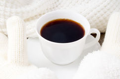 White cup with hot coffee and woolen mittens Royalty Free Stock Photos
