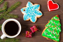 White Cup with hot drink and christmas gingerbread. On wooden brown background .The view from the top Royalty Free Stock Photo