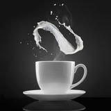 White cup with hot liquid and milk splash on black Royalty Free Stock Images