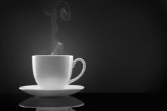 White cup with hot liquid and steam on black Stock Photos