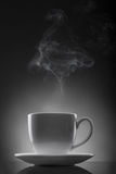 White cup with hot liquid and steam on black Stock Photography