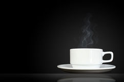 White cup with hot liquid and steam on black Stock Images