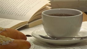 A white cup of really hot smoking coffee with open book on background stock footage