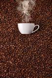 White cup with hot steam smoke at coffee beans Royalty Free Stock Image