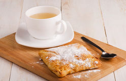 White cup of hot tea and fresh bun Royalty Free Stock Images