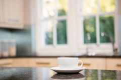 White cup on kitchen counter. View of white cup on kitchen counter Royalty Free Stock Photos