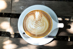 A white cup of latte from top view. Top view of hot latte coffee on classic wood table Royalty Free Stock Photo