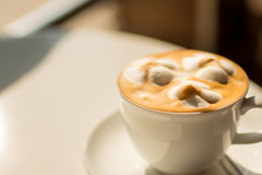 White cup of lattte coffee with sun rise lighting selective focu. A latte coffee with decorative froth in  white cup at golden hour with selective focus Stock Image