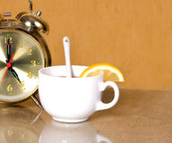 White cup of tea with lemon. White cup with lemon and hours, the tea party stock photos