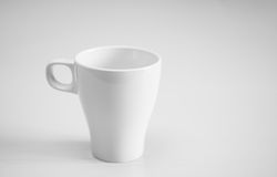 White cup on light wooden table. Horizontal format. Stock Photo