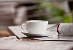 White cup with magazine on the wood table Stock Images