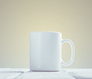 White cup mock-up inclined on wooden table royalty free stock image