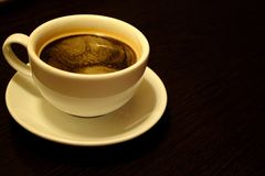 White cup with morning black coffee with foam on dark brown table with copy space. Breakfast in cafe background. Morning hot drink. Beginning of the day Stock Photos