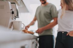 White cup near coffee machine with young happy couple on background stock photo