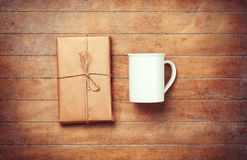 White cup and package on wooden table. Stock Images