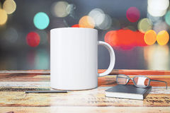 White cup with pen, diary and eyeglasses on wooden table. Mock up Stock Photography
