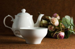 White cup and pot with roses Royalty Free Stock Photos