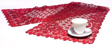White cup on red doily Royalty Free Stock Images
