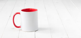 White cup with red handle and inside on table Stock Photo
