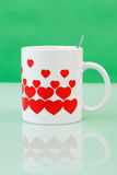 White cup with red hearts Royalty Free Stock Photos