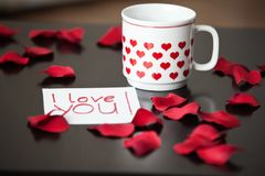 White cup with red hearts and an I-love-you-note on a black table, surrounded by red rose petals. White cup with red hearts and an I-love-you-note on a dark Royalty Free Stock Image