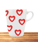 White cup with red hearts on wooden table isolated on white Royalty Free Stock Photos