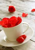 white cup with red petals of roses on old wooden Stock Photos