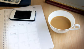 White cup of remain coffee in dim light office room with backgro. Und of cellphone, organizer book with text meeting for concept of busy working Royalty Free Stock Image