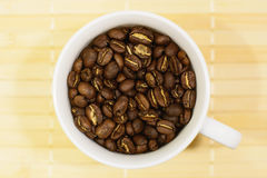 White cup with roasted coffee beans. A coffee cup full of brown roasted coffee beans on nature yellow color structured background Royalty Free Stock Photo