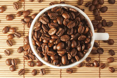 White cup with roasted coffee beans on the table Stock Photography