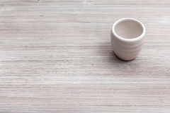 White cup for sake on gray brown wooden board Royalty Free Stock Photo