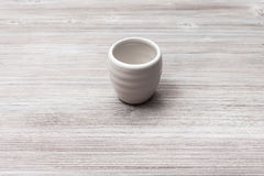 White cup for sake on gray brown wooden table Stock Image