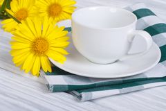 White cup and saucer with bouquet of daisies Stock Image