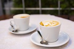 Two cup of coffee with milk cream in white cup. On terrace table royalty free stock image