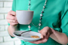 White cup and saucer with a drink in hand. At the woman in the green dress closeup Stock Photo