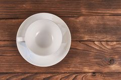 White cup and saucer. Empty white Cup and saucer with delicate ornament on wooden background, flat lay. Crockery for coffee and tea , chocolate, espresso Royalty Free Stock Photos