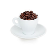 White cup and saucer filled with coffee beans. Isolated on white background Royalty Free Stock Photos
