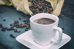 Fresh coffee decorated with chocolate sprinkles and coffee beans in the background stock photo