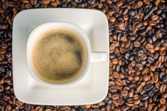 Cup of coffee on roasted coffee beans photographed from above with copy space stock photo