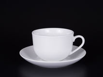 White cup on a saucer isolated on a black background. Royalty Free Stock Image