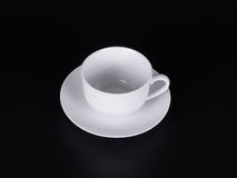 White cup on a saucer isolated on  black background Stock Image