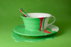White cup with a saucer and a spoon poured with red and green paint. On a green background Royalty Free Stock Image