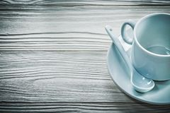 White cup saucer teaspoon on wooden board.  Stock Photo