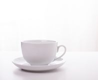 White cup and saucer. On a white top with a white background Stock Photos